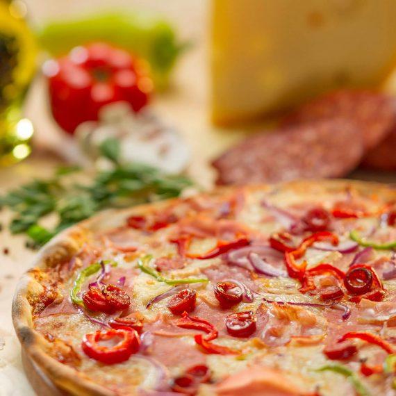 pizza Țărănească - sos de roșii, mozzarella, cârnați, șuncă, bacon, ardei gras, ceapă roșie