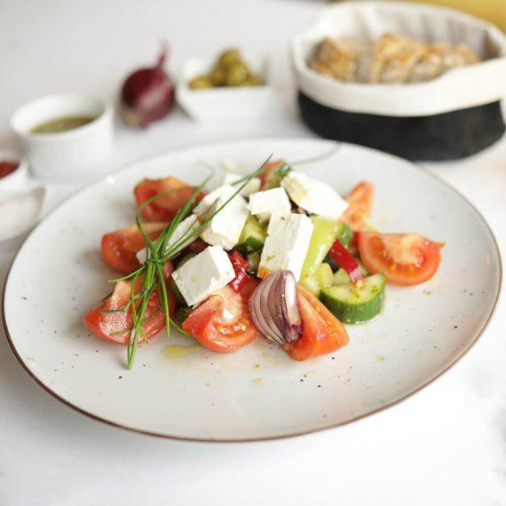 Salată grecească după rețetă tradițională: ulei de măsline Kalamata, brânză feta de capră, castraveți, ardei gras, roșii, măsline, ceapă